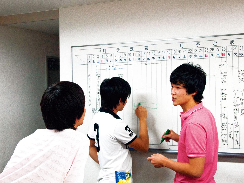 受付横の白板を使って、数IIIの議論をかわす生徒達の様子